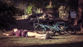 Miastowa młoda kobieta na rowerze ma przerwę na parkowej trawie Zdjęcia Stock