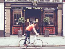 Miastowa scena cyklisty odprowadzenie przed Angielskim pubem Obrazy Stock