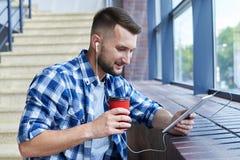 Miastowego brodatego mężczyzna słuchająca muzyka podczas gdy używać pastylkę Zdjęcia Stock