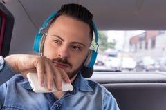 Miastowy biznesmen jest ubranym drelichową koszula na tylnym siedzeniu samochodowy słuchanie muzyka na smartphone Pojęcie dążenia obrazy royalty free