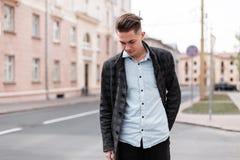 Miastowy elegancki młody facet z modną fryzurą w modnych eleganckich ubraniach blisko roczników domów outdoors Biznesowe facet po zdjęcie royalty free