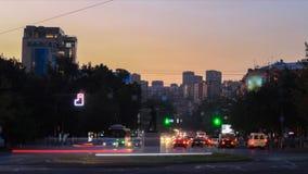 Miastowy krajobraz samochody i ludzie z długimi ujawnieniami przeciw tłu budynki, drzewa i niebieskie niebo, dzień zbiory