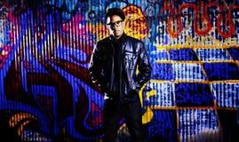 Miastowy mężczyzna przed graffiti ścianą. zdjęcie royalty free