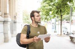 Miastowy mężczyzna z pastylki komputerowy patrzeć daleko od w ulicie zdjęcia royalty free