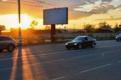 Miastowy ruch drogowy przy wieczór, światło słoneczne Samochodu i światła zmierzch na drodze Zdjęcia Royalty Free
