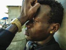 Miastowy styl życia portret młody smutnego i przygnębionego czarnego afrykanina Amerykański mężczyzna siedzi outdoors na rogu uli zdjęcia royalty free