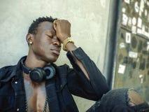Miastowy styl życia portret młody smutny i przygnębiony czarny afro Amerykański mężczyzna siedzi outdoors na rogu ulicego uczucia obrazy royalty free