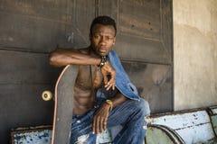 Miastowy styl ?ycia portret m?ody przystojny i atrakcyjny czarny afro Ameryka?ski deskorolkarza m??czyzny obsiadanie na miasta gr obrazy royalty free