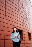 Miastowy stylowy poj?cie Portret modna nastoletnia dziewczyna z okularami przeciwsłonecznymi w jej rękach pozuje na miasto ulicie obrazy stock