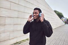 miastowy szczęśliwy uśmiechnięty afrykański mężczyzna jest ubranym czarnego hoodie na miasto ulicie w bezprzewodowych hełmofonach fotografia royalty free