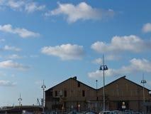 Miastowy widok dwa dachowego wierzchołka duzi budynki portem morskim, łódkowaci domy z wysokimi miasto lampami w przodzie, pod ch obrazy royalty free
