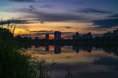 Miastowy zmierzch z sylwetkami miasto budynki na kolorowym nieba i jeziora tle zdjęcia royalty free