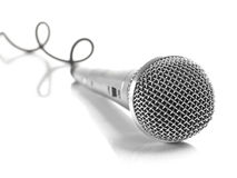 Mic with curled cable. A dynamic mic with a curled cable over white Royalty Free Stock Photos