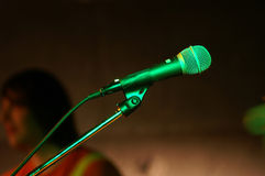 Mic in green. Microphone on stage, with concert lightning and the musician in the background Stock Photography