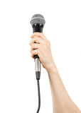 Mic in hand. Woman's hand holding a microphone. isolated on white background Stock Photos