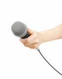 Mic in hand. Woman's hand holding a microphone. isolated on white background Stock Images