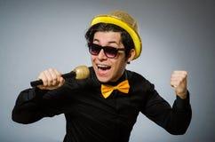 有mic的滑稽的人在卡拉OK演唱概念 库存图片