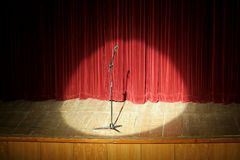 Mic on stage. Microphone on wooden stage, red curtain in background, spot light Royalty Free Stock Photo