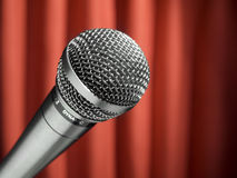 Mic on stage. A dynamic microphone over a red background Royalty Free Stock Photos