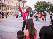 Michael Jackson tribute artist finishes a number on the plaza in. Young man in red shirt and black jeans ends a street performance on the place at the Hotel de Stock Photos