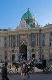 Michaelator. Street scene in Vienna, Austria. A horse carriage crosses in front of a historic palace in vienna Royalty Free Stock Photography