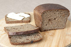 Miche de pain coupée en tranches sur une planche à découper Photo stock