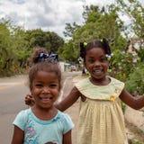 Miches, República Dominicana, o 16 de abril de 2019/duas meninas coloridas locais novas que jogam com baloons no lado da estrada imagens de stock royalty free