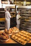 Michetta en zoet voedsel op een lijst terwijl mannelijke en vrouwelijke bakker die op achtergrond werken royalty-vrije stock fotografie