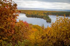 Michigan Autumn Scenic Overlook Panorama. Vibrant autumn color in the northern Michigan forest with the vast blue waters of Lake Superior in the background royalty free stock image