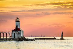 Michigan City, Indiana Light and Chicago. The setting sun back lights the lighthouse shining at Michigan City, Indiana with the Chicago skyline silhouetted on stock photo