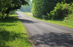 Michigan Country Roads 19. This Michigan country road is lines with many trees along the way. Interesting patterns left by tree shadows land on the road and make royalty free stock photo