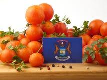 Michigan-Flagge auf einer Holzverkleidung mit den Tomaten lokalisiert auf einem Whit Lizenzfreies Stockfoto