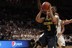 Michigan guard Trey Burke. Michigan guard Trey  Burke drives to the basket Royalty Free Stock Photography