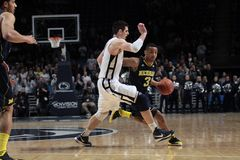 Michigan's #3 Trey Burke drives to the basket. Against Penn State Stock Photos