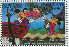 Mickey and Minnie. MALDIVE ISLANDS - CIRCA 1996: stamp printed by Maldive Islands, shows Mickey, Minnie, in Chinese Garden, circa 1996 Stock Images