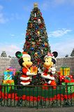 Mickey and minnie mouse christmas at disneyland hong kong. Figures of mickey mouse exchanging christmas gift with a excited minnie mouse on display at disneyland royalty free stock images