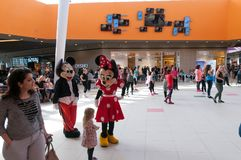 Mickey and Minnie mouse figurines  cheering up the zumba dancers. In the city mall Stock Photo