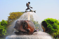 Mickey mouse. Bronze statue of mickey mouse with skate board raised up on the fountain. location : disneyland, hong kong Stock Photography