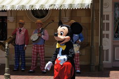 Mickey Mouse at Disneyland. While a band plays in the background Royalty Free Stock Image