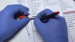 Micoplasma, medico che controlla malattia nello spazio in bianco del laboratorio, mostrante campione di sangue in tubo archivi video