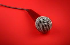Micrófono con cierre del alto ángulo del cable para arriba sobre rojo Fotografía de archivo
