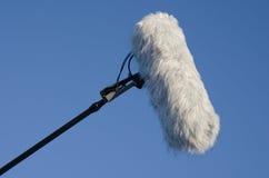 Micrófono con el parabrisas con el fondo del cielo azul Foto de archivo libre de regalías