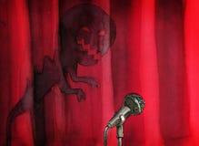 Micrófono contra la cortina roja de la etapa con la sombra del frightfull Imagenes de archivo