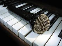 Micrófono en claves del piano Imagen de archivo