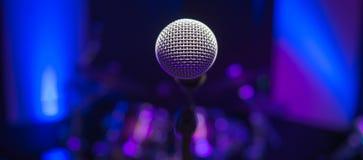 Micrófono en etapa contra un fondo del auditorio Fotografía de archivo libre de regalías