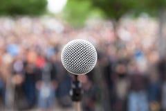 Micrófono en foco contra la muchedumbre borrosa Reunión política fotografía de archivo