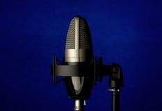 Micrófono en fondo azul Fotos de archivo