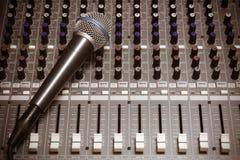 Micrófono en fondo del mezclador de sonidos Imagen de archivo libre de regalías