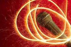 Micrófono en fondo y sparkler rojos Imagenes de archivo