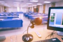 Micrófono en la tabla con el ordenador en sala de seminarios Imagen de archivo